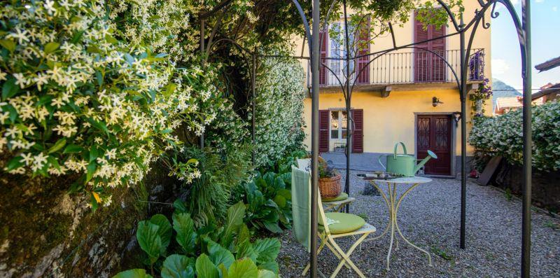 Giardino con piante rigogliose e tavolino - Charming House Bice