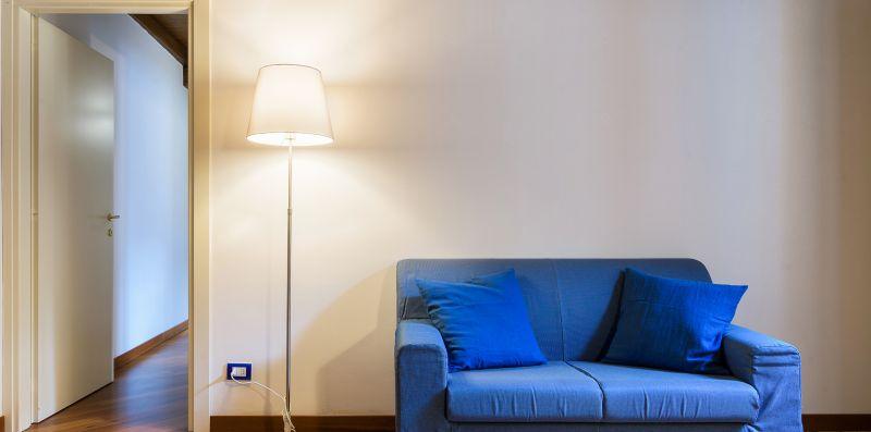 Divano biposto blu con cuscini e lume - Contrada San Giacomo
